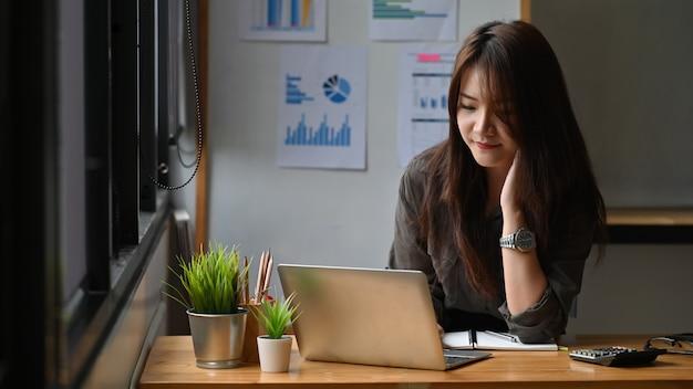 Jeune femme d'affaires travaillant avec un ordinateur portable.
