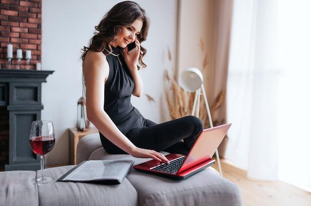 Jeune femme d'affaires travaille à la maison. le modèle latractif de cheerfu est assis sur le bord de la table et parle au téléphone. taper sur le clavier de l'ordinateur portable. verre de vin rouge sur table.