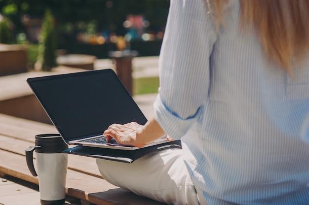 Une jeune femme d'affaires travaille avec un ordinateur portable dans une chemise bleue dans la rue dans un parc