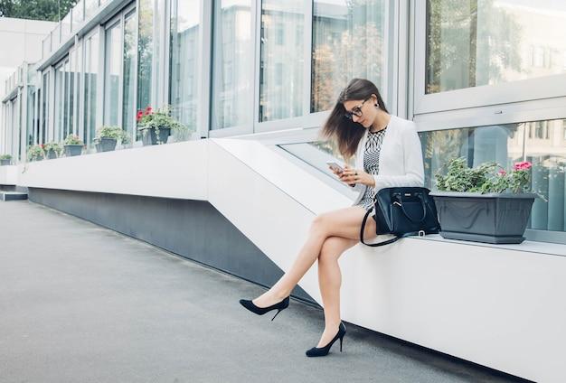 Jeune femme d'affaires utilisant son smartphone assis par centre d'affaires