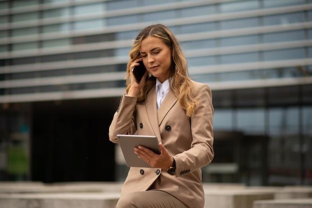 Jeune femme d'affaires utilisant son téléphone portable tout en tenant une tablette en plein air