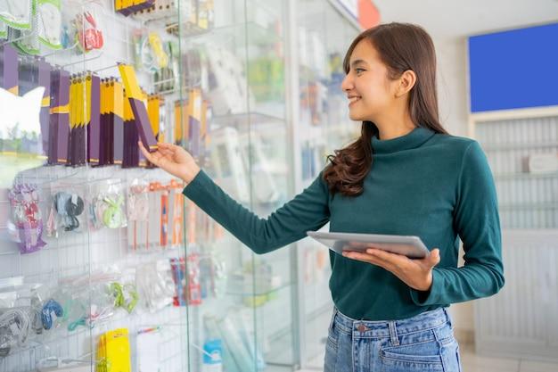 Jeune femme d'affaires utilisant une tablette tout en tenant des articles de produits accessoires pour téléphones portables à proximité