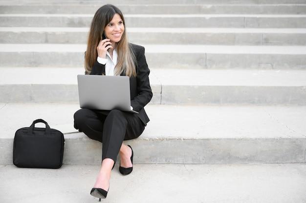 Jeune, femme affaires, utilisation, ordinateur portable, dans, ville
