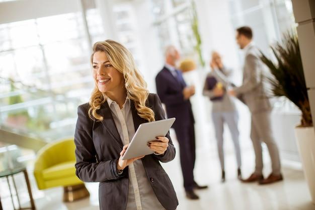 Jeune, femme affaires, utilisation, à, tablette, dans, bureau, tandis que, autres, hommes affaires, parler, dans, fond