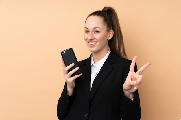 Jeune, femme affaires, utilisation, téléphone portable, sur, isolé, mur, sourire, et, projection, signe victoire