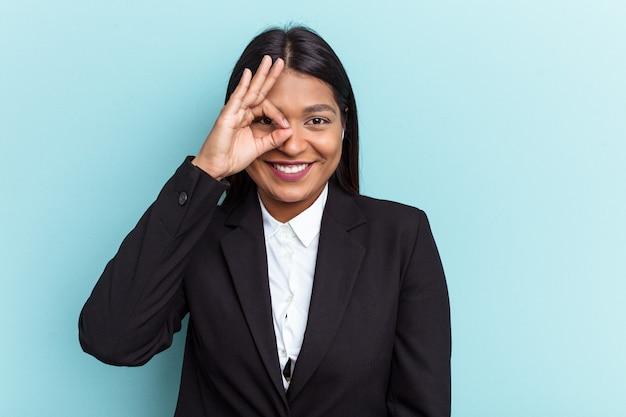 Jeune femme d'affaires vénézuélienne isolée sur fond bleu excitée en gardant un geste ok sur les yeux.