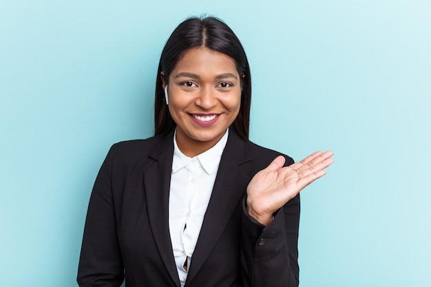 Jeune femme d'affaires vénézuélienne isolée sur fond bleu montrant un espace de copie sur une paume et tenant une autre main sur la taille.