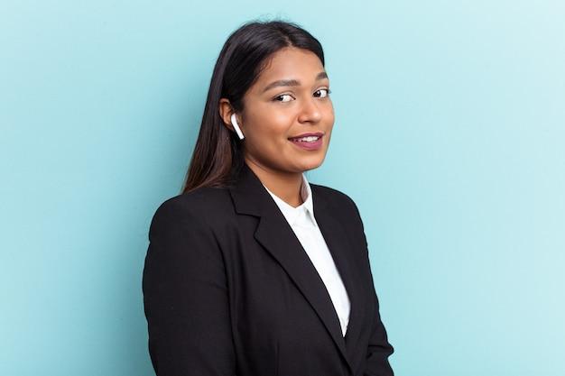 Jeune femme d'affaires vénézuélienne isolée sur fond bleu regarde de côté souriante, gaie et agréable.