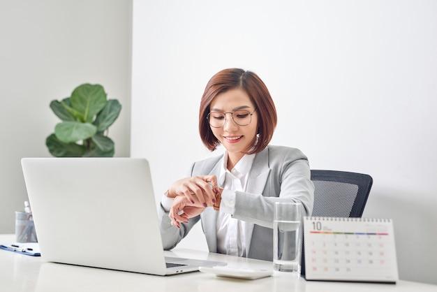Jeune femme d'affaires vérifiant l'heure sur sa montre-bracelet sur le lieu de travail. gestion du temps