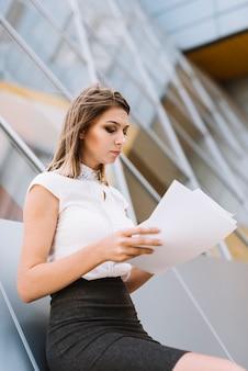 Jeune femme d'affaires vetu lisant des documents