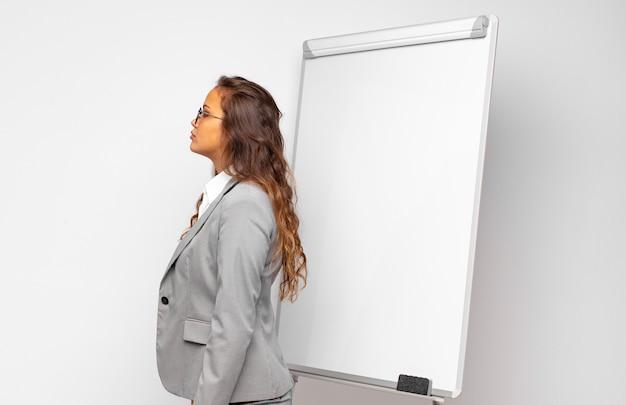 Jeune femme d'affaires sur la vue de profil à la recherche de copier l'espace à venir, penser, imaginer ou rêver