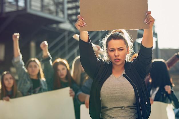 Jeune femme avec une affiche vierge devant des personnes qui protestaient contre les droits des femmes et l'égalité dans la rue. réunion sur le problème au travail, la pression masculine, la violence domestique, le harcèlement. espace de copie.
