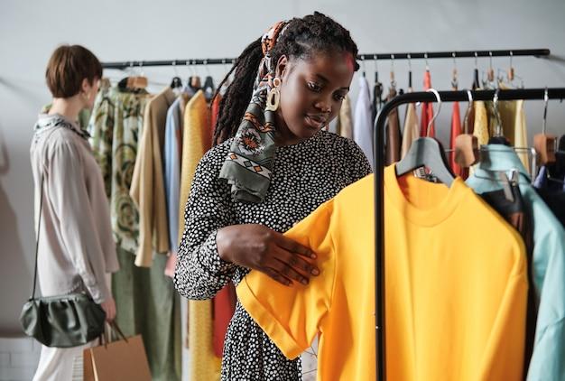 Jeune femme africaine achetant de nouveaux vêtements pour elle-même dans le centre commercial