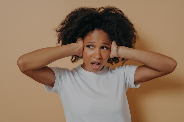 Jeune femme africaine agacée couvrant ses oreilles et gardant la bouche ouverte isolée sur fond beige