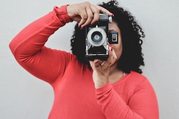 Jeune femme africaine à l'aide de l'appareil photo vintage à l'extérieur dans la ville - focus sur la lentille