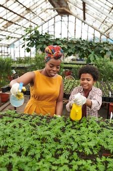 Jeune femme africaine arrosant des plantes avec un petit garçon pendant leur travail en serre
