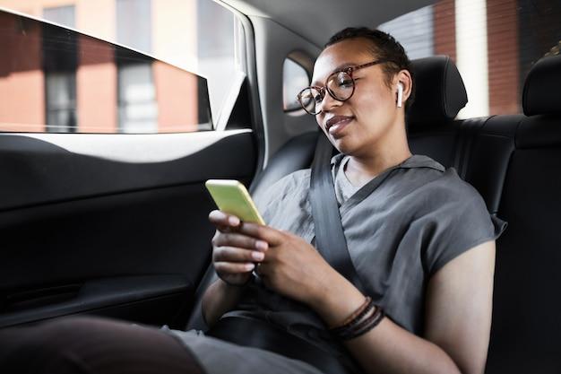 Jeune femme africaine assise sur la banquette arrière et lisant un message sur son téléphone portable pendant son voyage en voiture