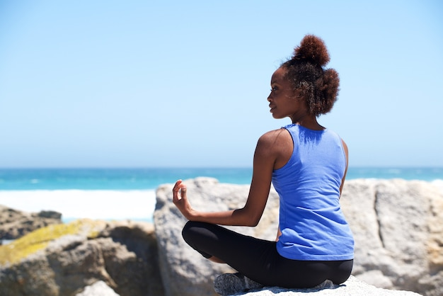 Jeune femme africaine assise sur la plage dans la pose d'yoga