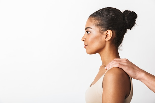 Jeune femme africaine assise tandis que la main de l'homme tenant ses épaules isolé sur blanc