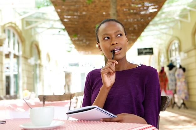 Jeune femme africaine au café, notes d'écriture