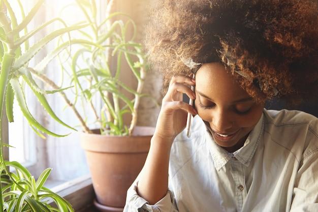 Jeune femme africaine aux cheveux bouclés parler au téléphone