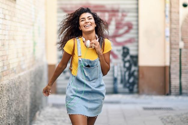 Jeune femme africaine avec un casque marchant en plein air