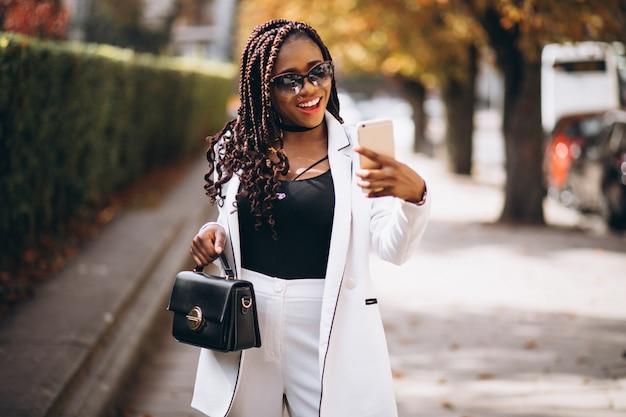 Jeune femme africaine en costume blanc à l'aide de téléphone