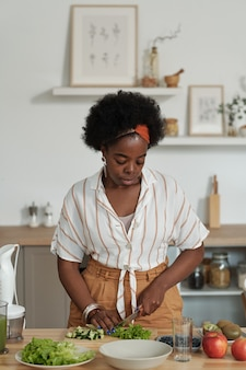 Jeune femme africaine coupant des légumes pour une salade végétarienne