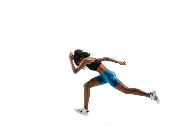 Jeune femme africaine en cours d'exécution isolé sur fond de studio blanc. une coureuse ou joggeuse. silhouette d'athlète de jogging