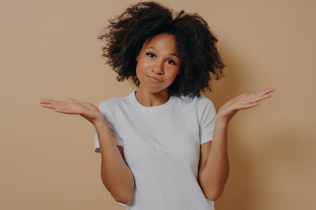 Jeune femme africaine douteuse levant les paumes avec hésitation et regardant la caméra avec une expression de visage perplexe, une femme métisse étant incertaine et ayant des doutes en posant contre un mur beige