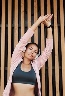 Jeune femme africaine écoutant de la musique dans des écouteurs sans fil levant les bras et faisant de l'exercice pendant...