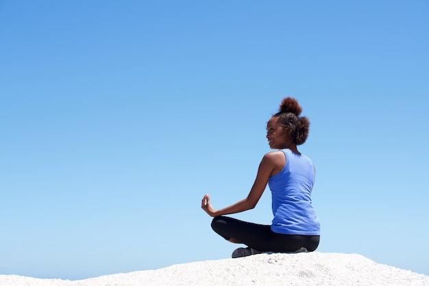 Jeune femme africaine, faire du yoga à la plage