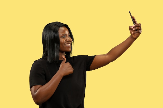 Jeune femme africaine isolée sur fond de studio jaune, expression faciale