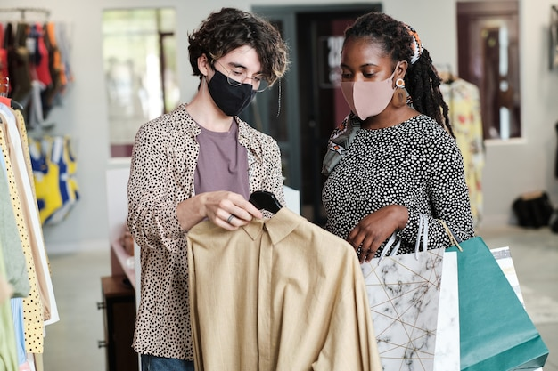 Jeune femme africaine en masque achetant de nouveaux vêtements avec l'aide d'un vendeur dans le magasin