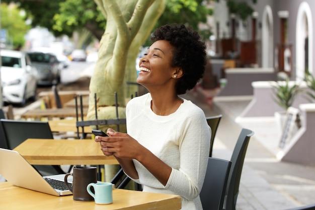Jeune femme africaine, riant avec téléphone portable au café