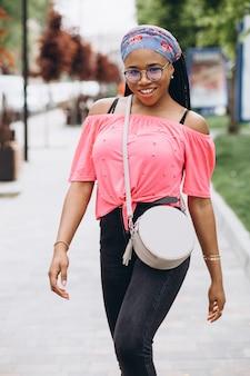 Jeune femme africaine avec un sac élégant portant des lunettes à l'extérieur.