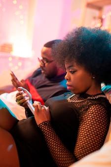Jeune femme africaine sérieuse et son petit ami assis sur un canapé et défilement dans leurs smartphones tout en surfant sur le net
