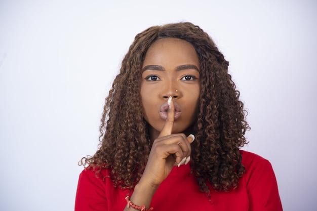 Jeune femme africaine avec son doigt sur sa bouche, faisant des gestes pour le silence