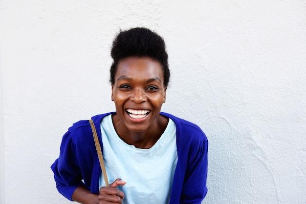 Jeune femme africaine souriant contre un mur blanc