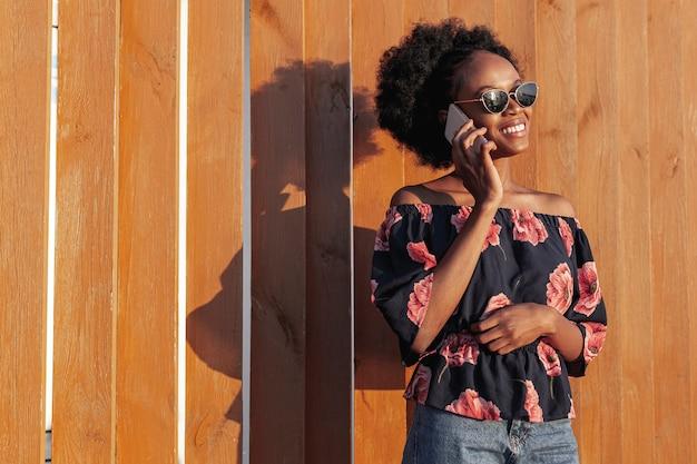 Jeune femme africaine souriante tout en parlant au téléphone