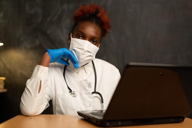 Jeune femme africaine en uniforme médical avec ordinateur portable