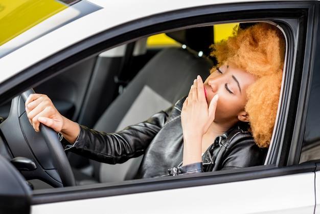Jeune femme africaine en veste de cuir se sentant endormie en conduisant la voiture