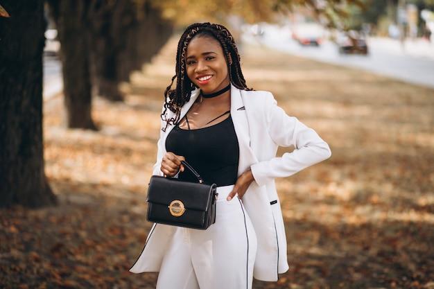 Jeune femme africaine vêtue d'un costume blanc dans le parc