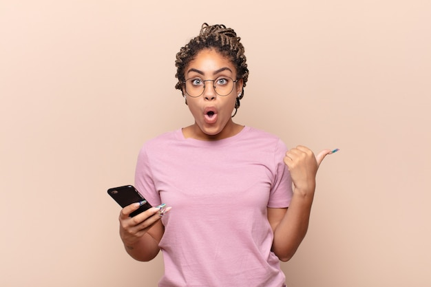 Jeune femme afro à l'air étonné d'incrédulité, pointant un objet sur le côté et disant wow, incroyable. concept de téléphone intelligent
