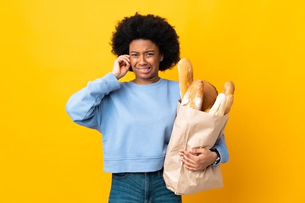Jeune femme afro-américaine acheter quelque chose de pain isolé sur jaune frustré et couvrant les oreilles
