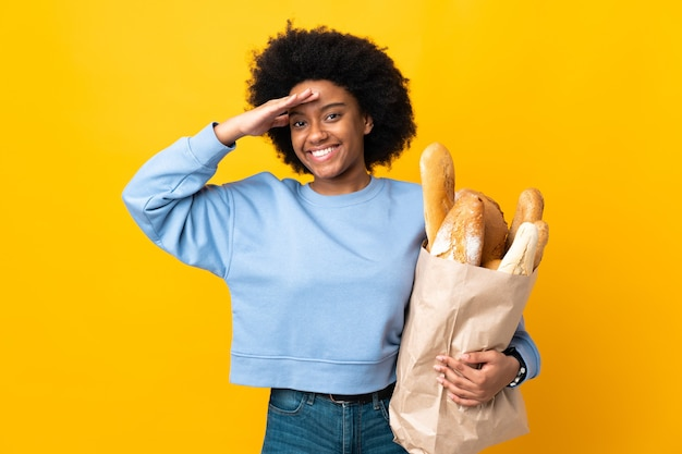 Jeune femme afro-américaine acheter quelque chose de pain isolé sur jaune saluant avec la main avec une expression heureuse