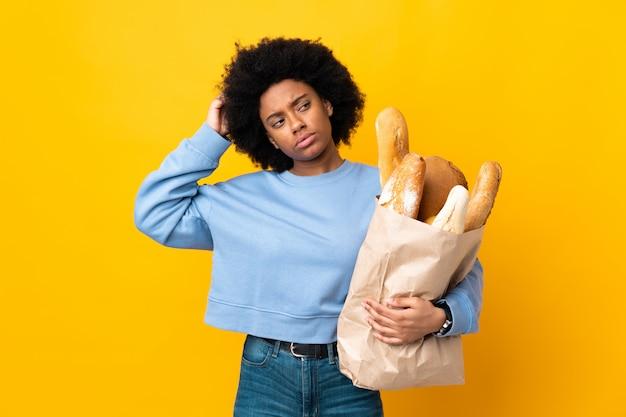 Jeune femme afro-américaine acheter quelque chose de pain isolé sur mur jaune ayant des doutes tout en se grattant la tête