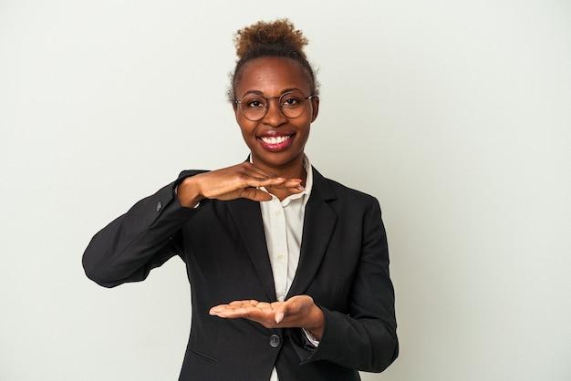 Jeune femme afro-américaine d'affaires isolée sur fond blanc tenant quelque chose avec les deux mains, présentation du produit.