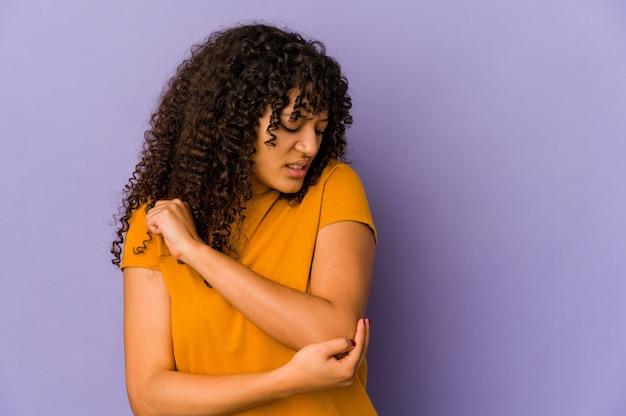 Jeune femme afro-américaine africaine isolée de massage du coude, souffrant après un mauvais mouvement.