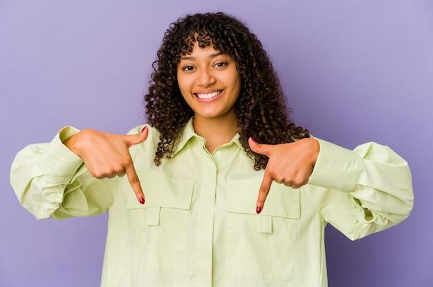 Jeune femme afro-américaine africaine isolée pointe vers le bas avec les doigts, sentiment positif.